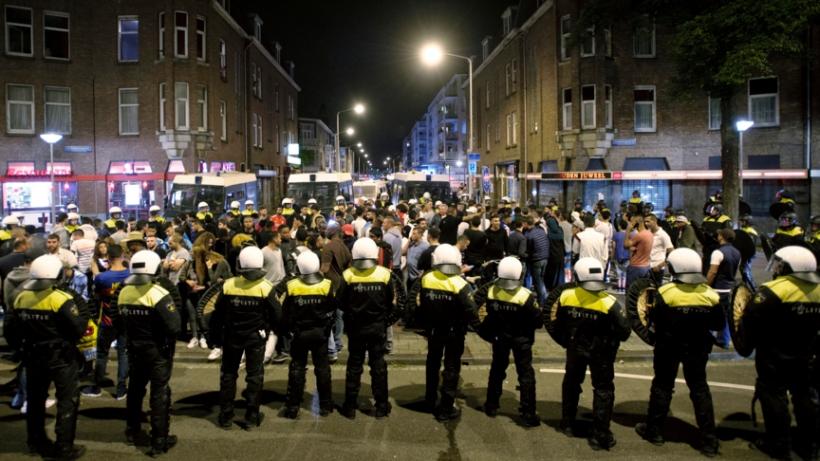 2015-07-03 00:00:00 DEN HAAG - Leden van de Mobiele Eenheid (ME) vormen een linie om mensen in te sluiten op het Hobbemaplein in de Haagse Schilderswijk. Hier gold een samenscholingsverbod, nadat drie dagen op rij rellen zijn uitgebroken. Ongeveer honderd mensen werden gearresteerd. Betogers gingen de straat op naar aanleiding van de dood van Mitch Henriquez, die stikte en stierf door toedoen van de agenten die hem arresteerden. ANP MARTEN VAN DIJL